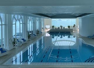 rectangular blue swimming pool inside white building