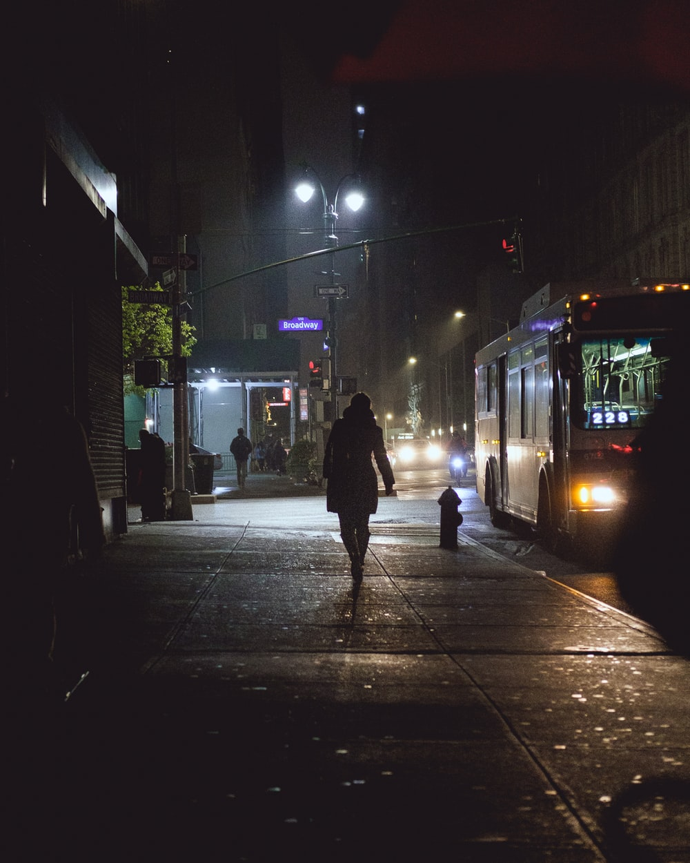 person walking on pathway near bus and vehicles during night time