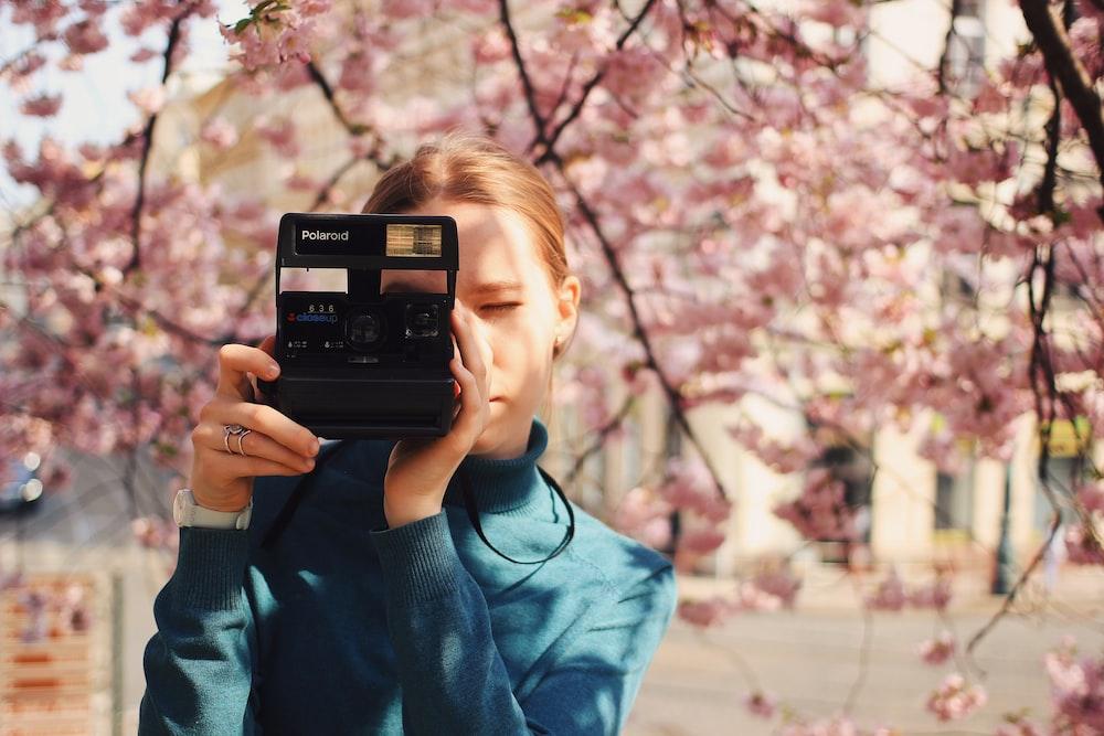 woman holding Polaroid land camera