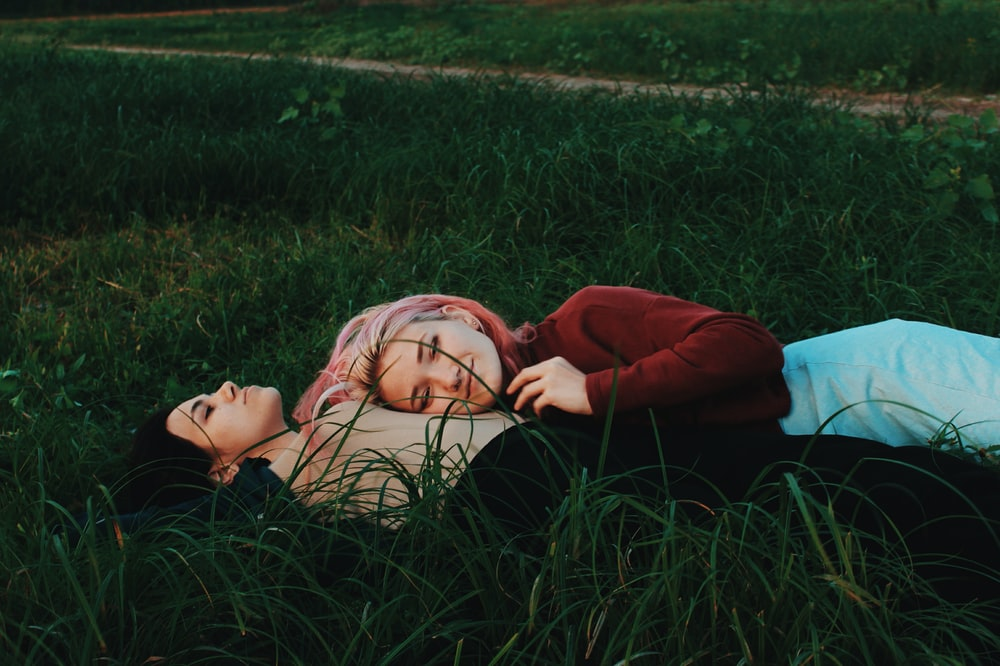 two women lying on green grass