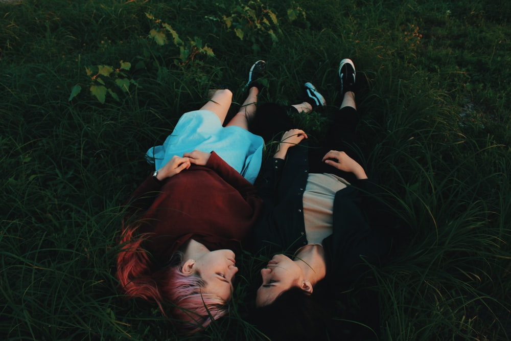 two women lying on grasses