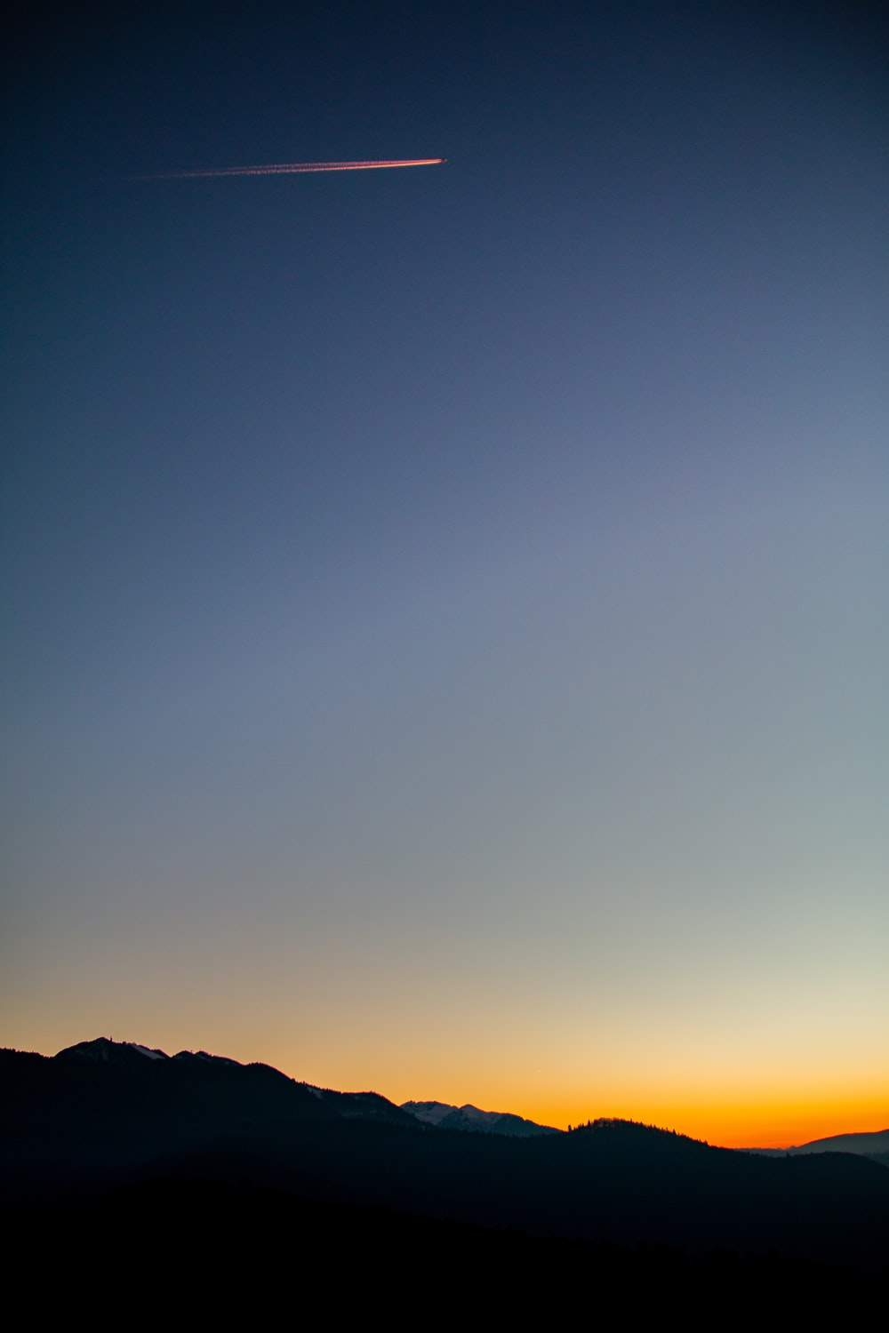 silhouette of mountain under blue and orange skies