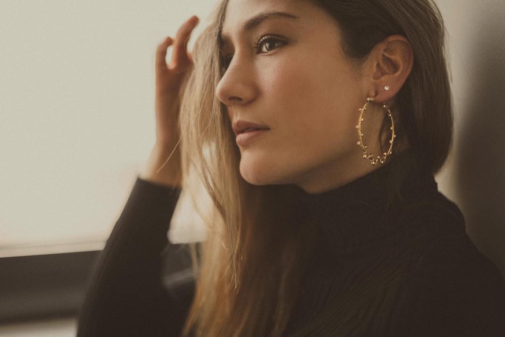 woman wearing black turtleneck long-sleeved top and hoop earring