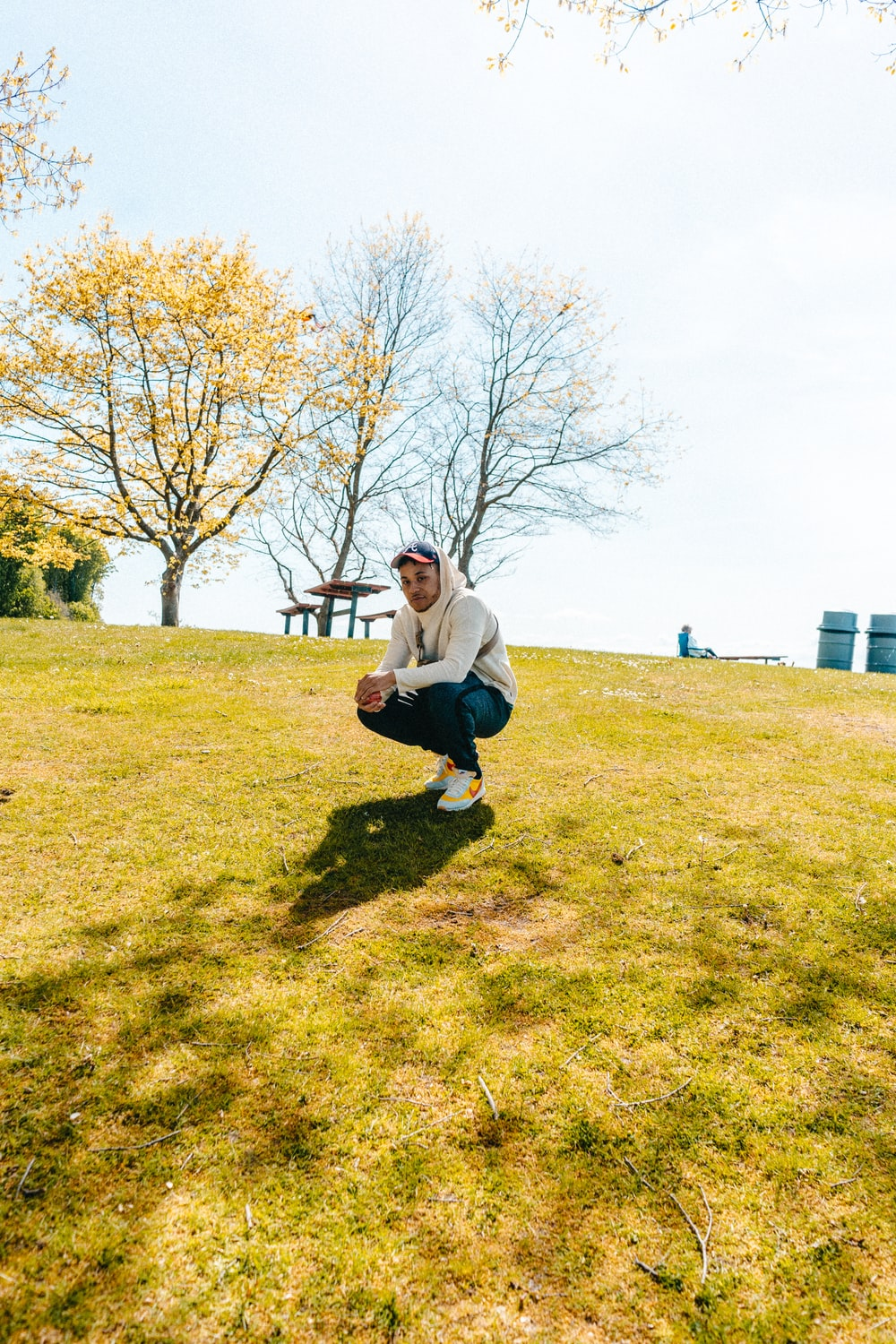 man in white jacket squatting on green grass lawn