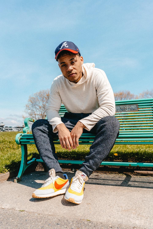man wearing grey pants sitting on bench