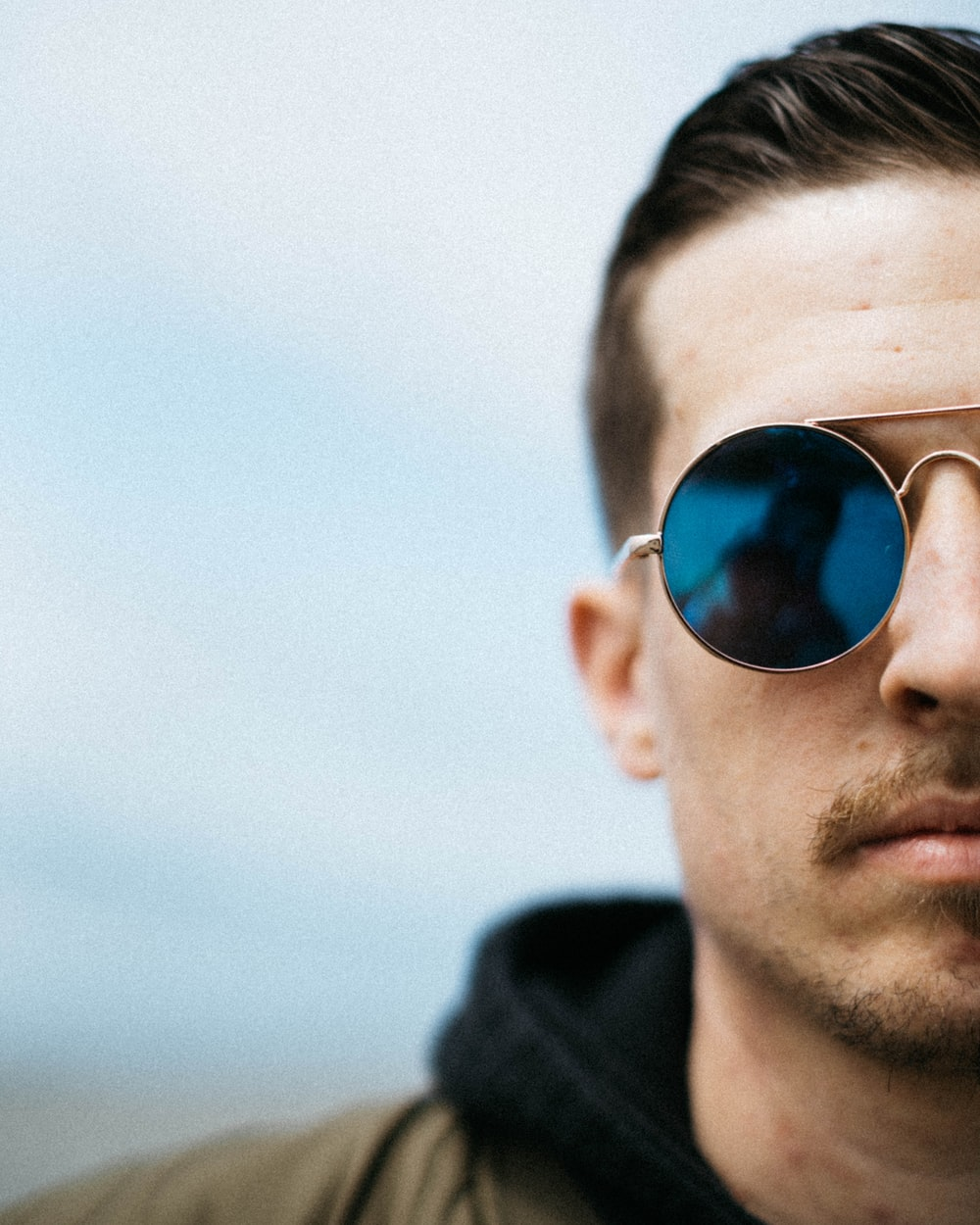 man wearing gold-framed sunglasses with blue lens