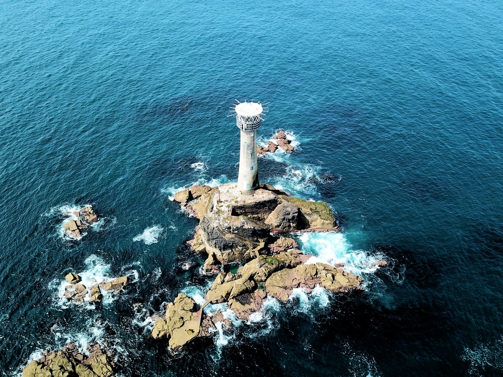aerial view of lighthouse surrounded with water