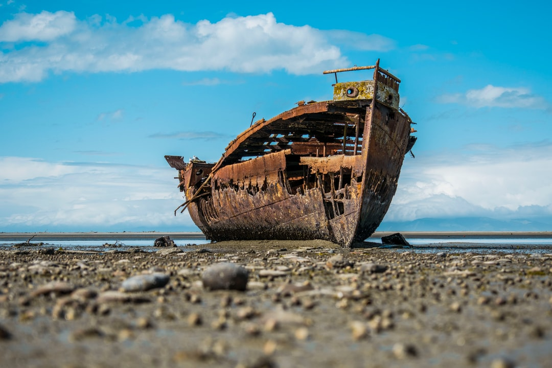 Abadoned boat on shore.