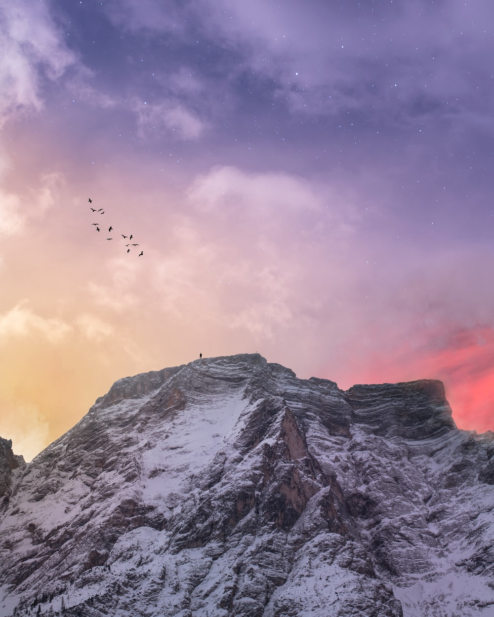 mountain covered with snow under blue and orange skies