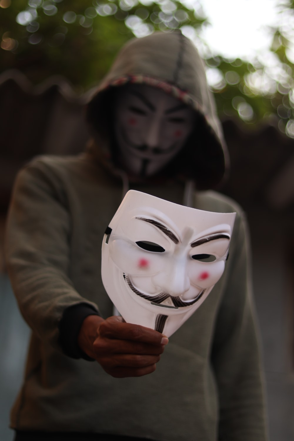 person standing and wearing Guy Fawke mask and holding another one