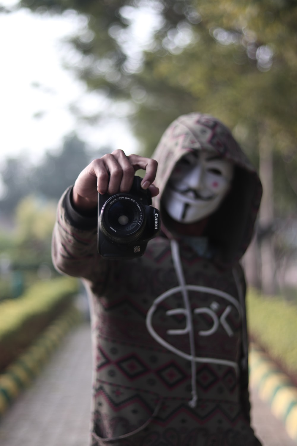 person standing and wearing guy fawkes mask holding DSLR camera