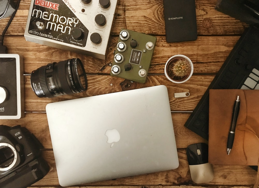 silver MacBook near camera lens