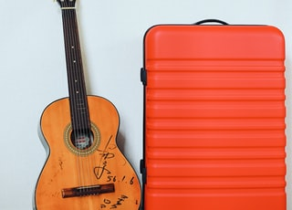 red hard-shell luggage bag beside guitar