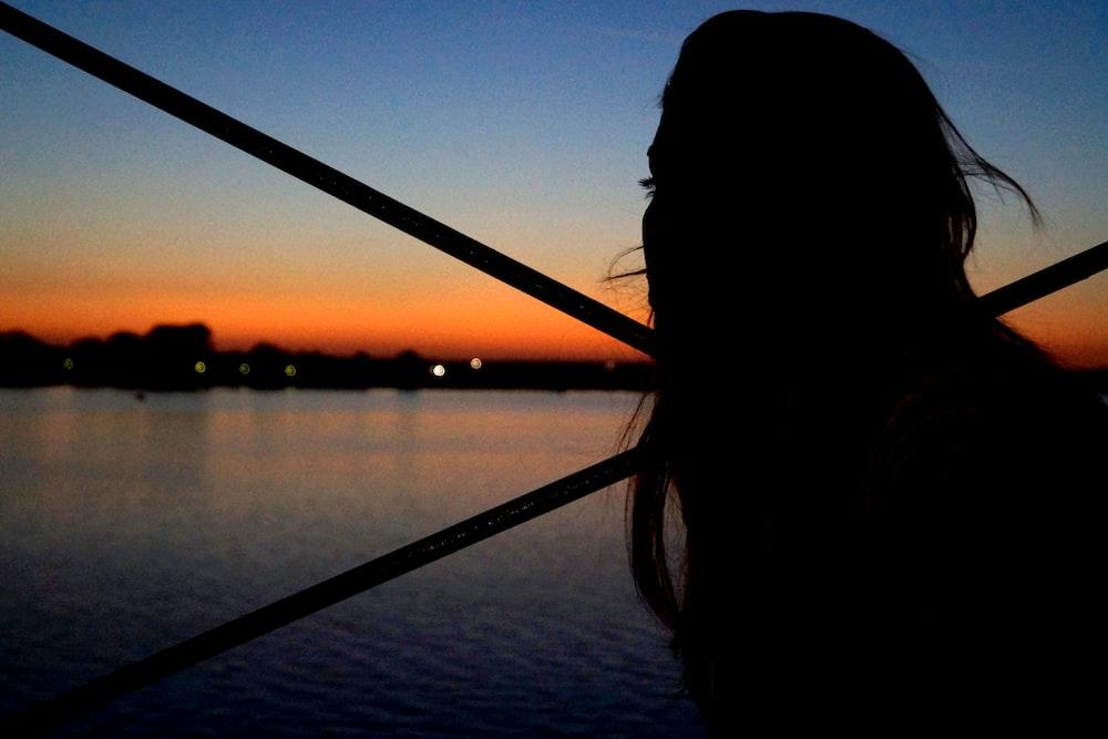 silhouette of woman beside sea