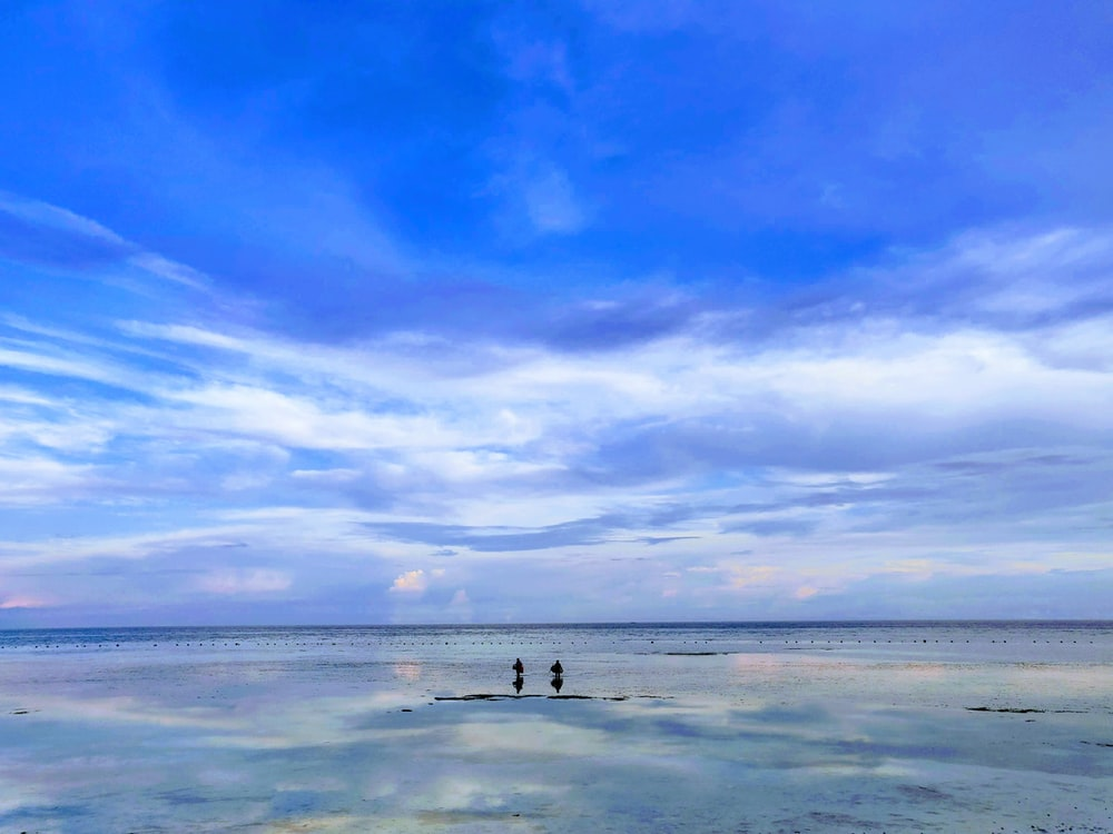 blue calm sea under blue and white skies