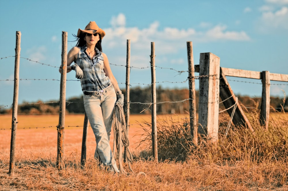 woman in sleeveless button-up top and cowboy hat leaning on barbed-wire fence