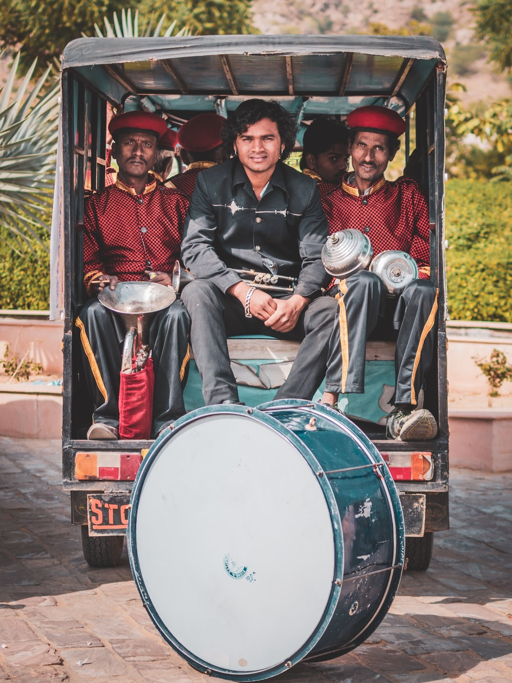 people in band uniform riding in auto rickshaw