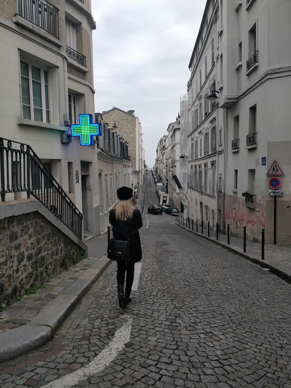 woman in black coat walking in alley