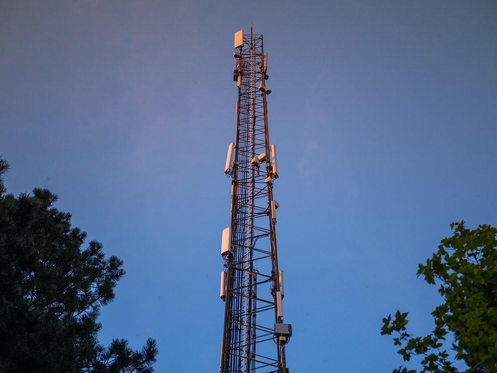 brown satellite tower near green trees