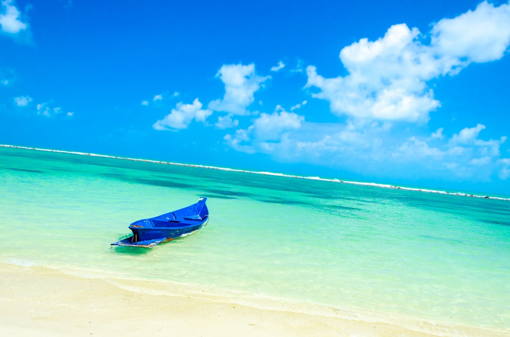 landscape photo of a blue boat on a beach