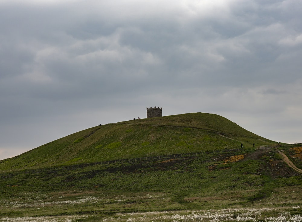 landscape photo of a castle on a green hill