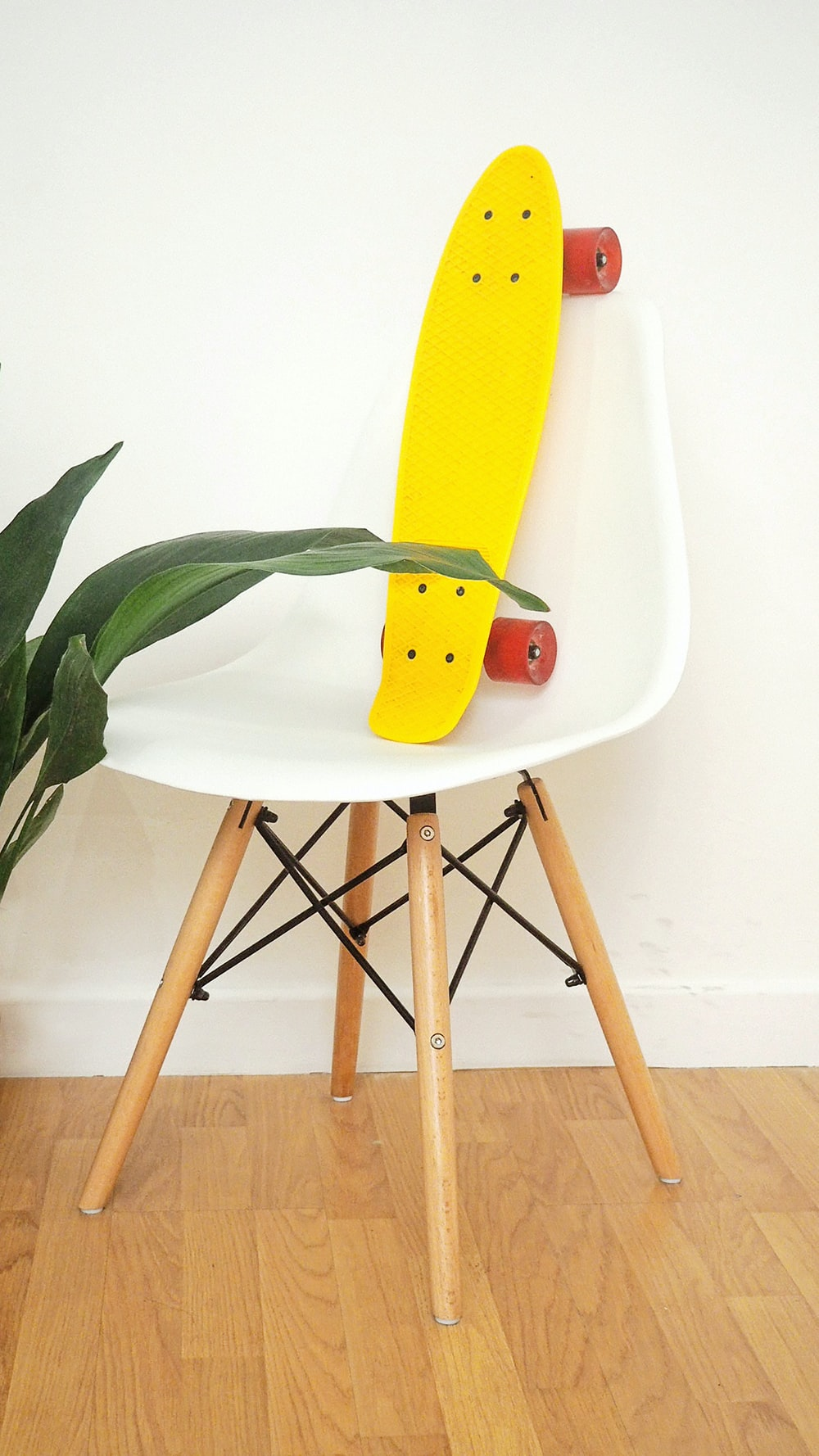 yellow penny board in white plastic chair