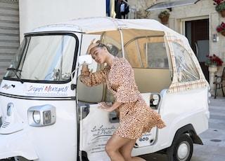 woman looking at white auto rickshaw wing mirror