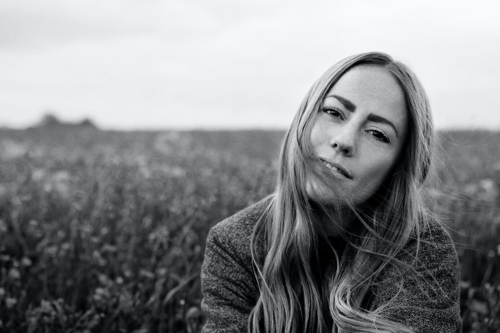 grayscale photography of woman surrounded with plants