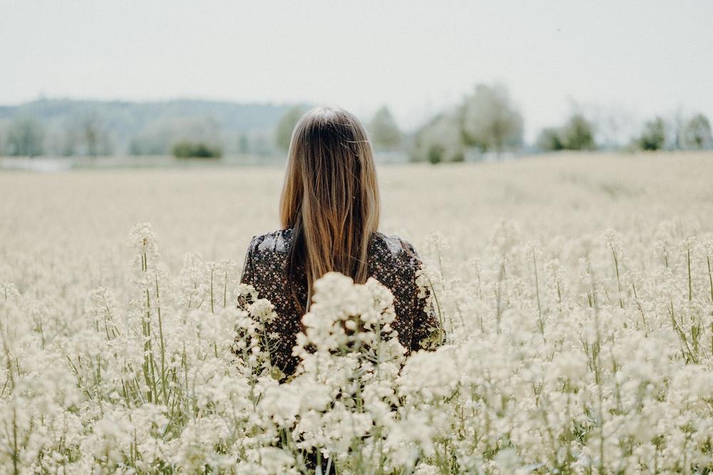 woman standing on white flower field
