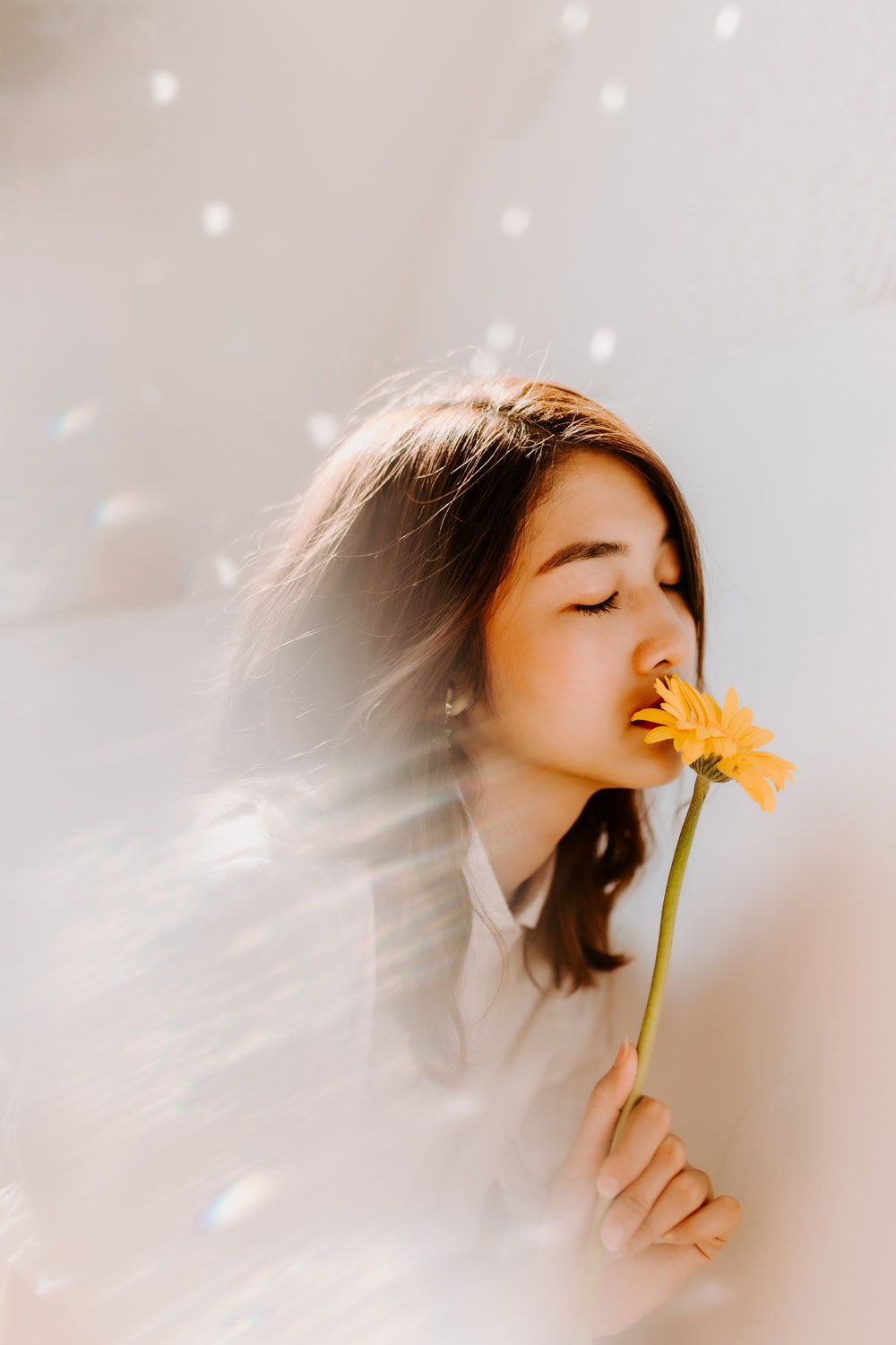 woman smelling on yellow flower