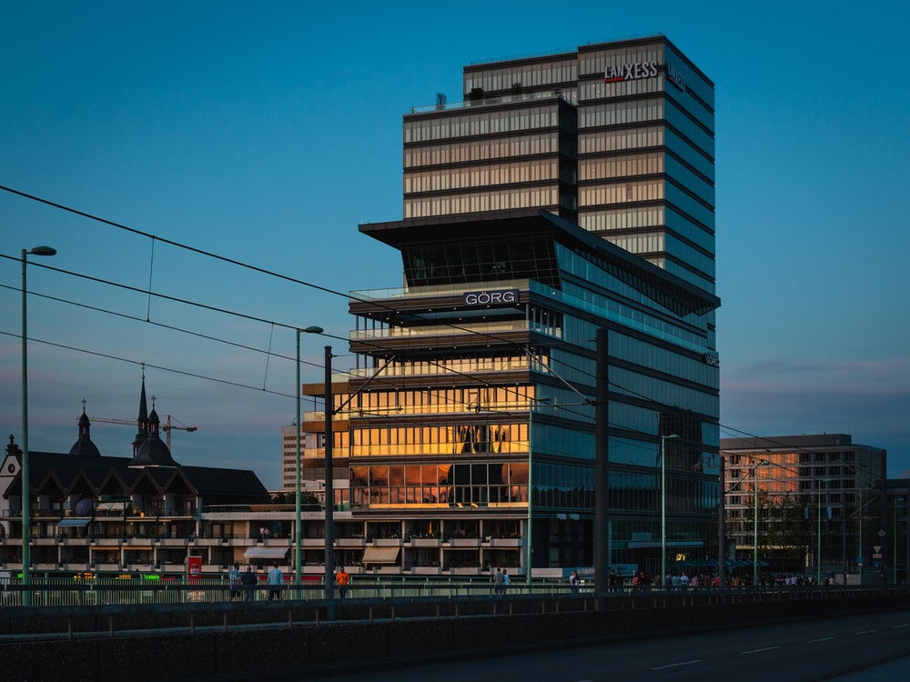 people walking on bridge near glass paneled building