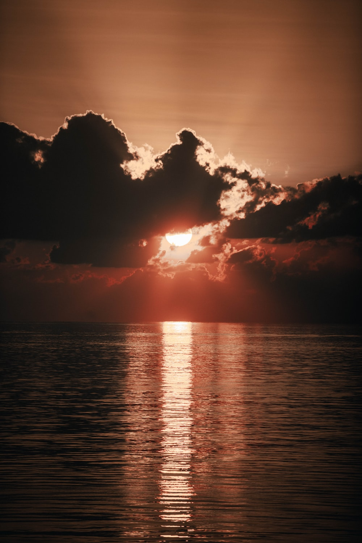 orange setting sun behind black clouds over the sea