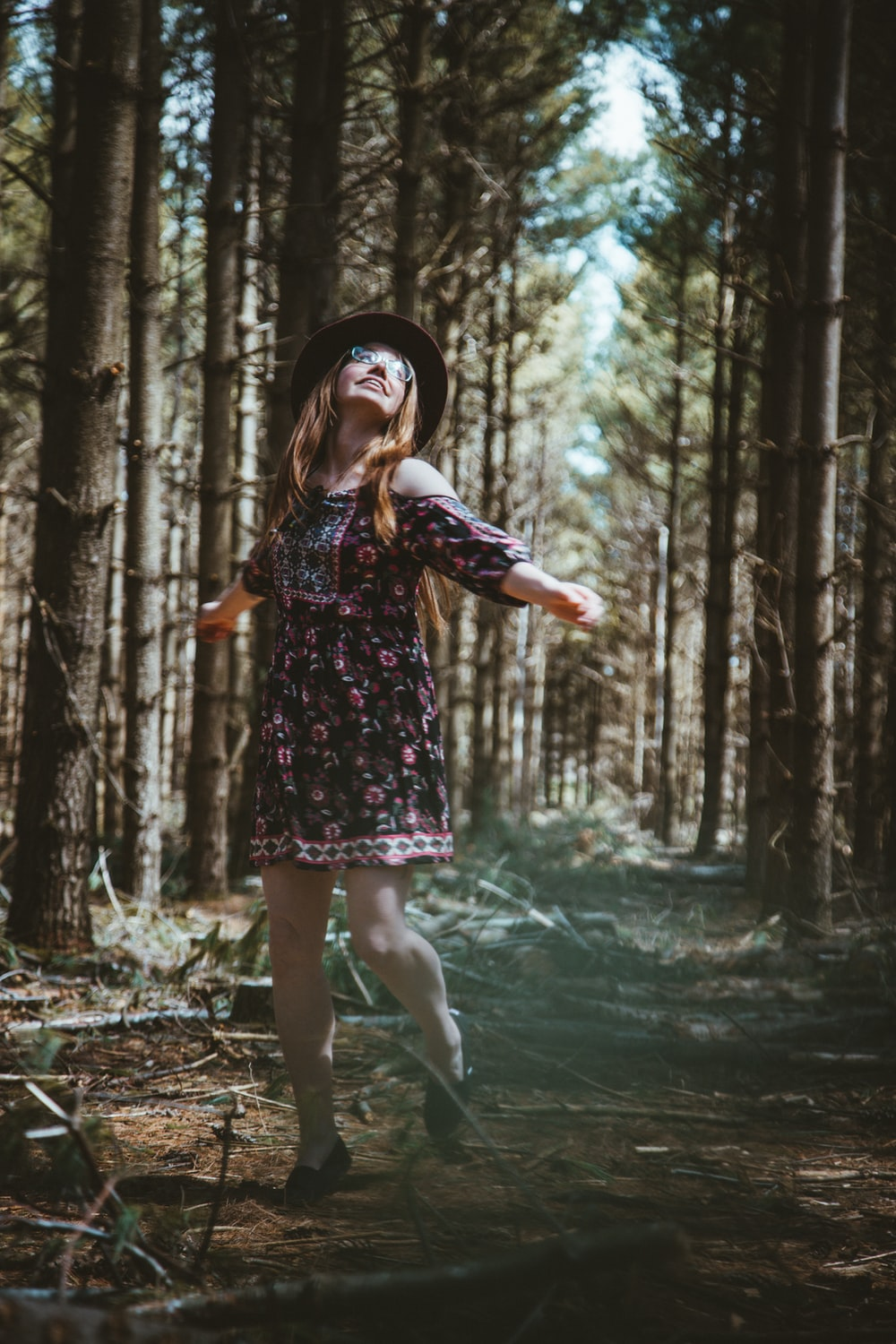 woman in multicolored floral dress standing in woods