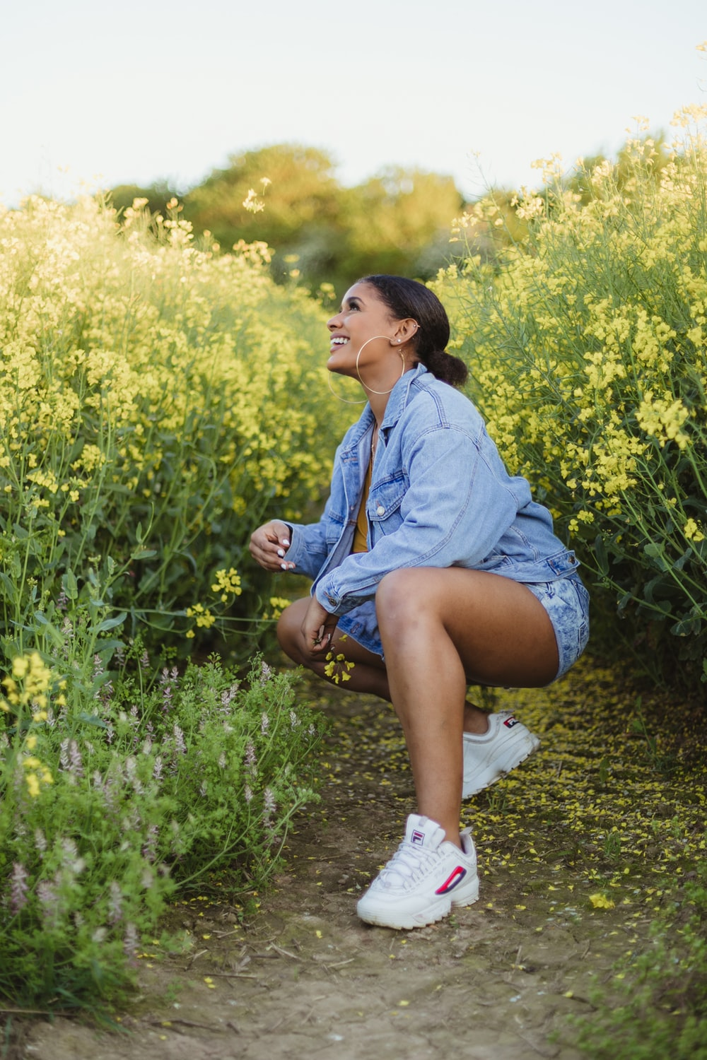 smiling woman sitting between yellow flowers