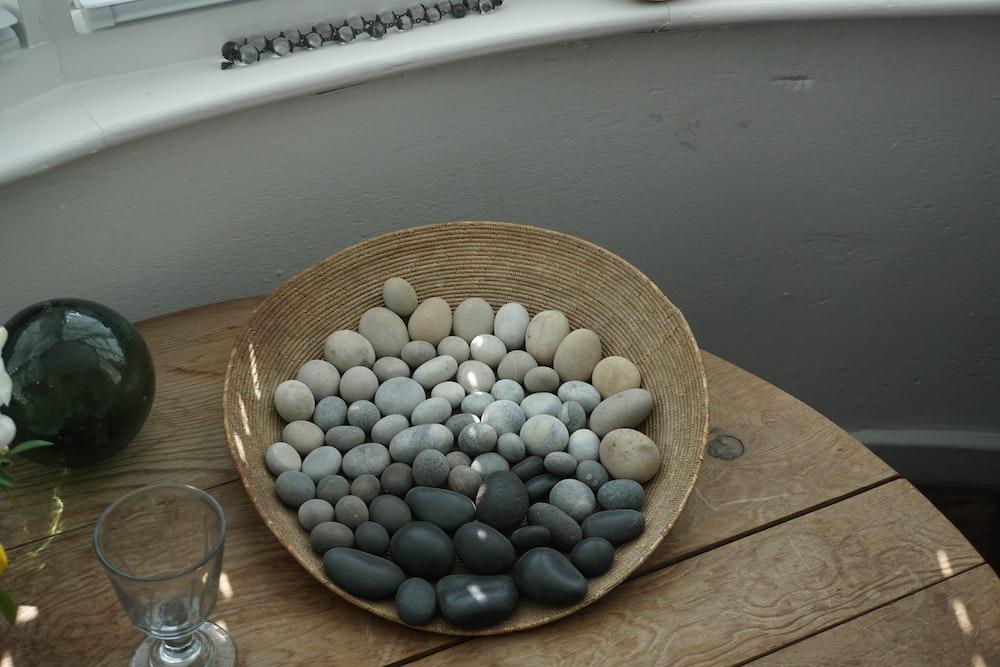 pebbles on wicker plate beside drinking glass