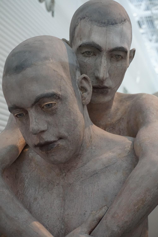 two men hugging statue