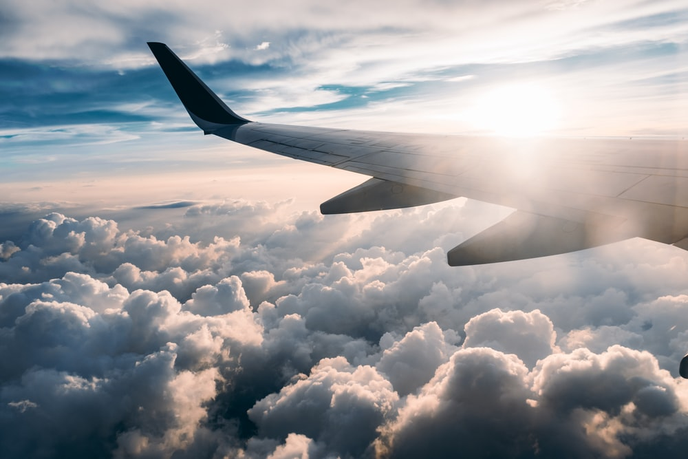 flying airplane over white clouds