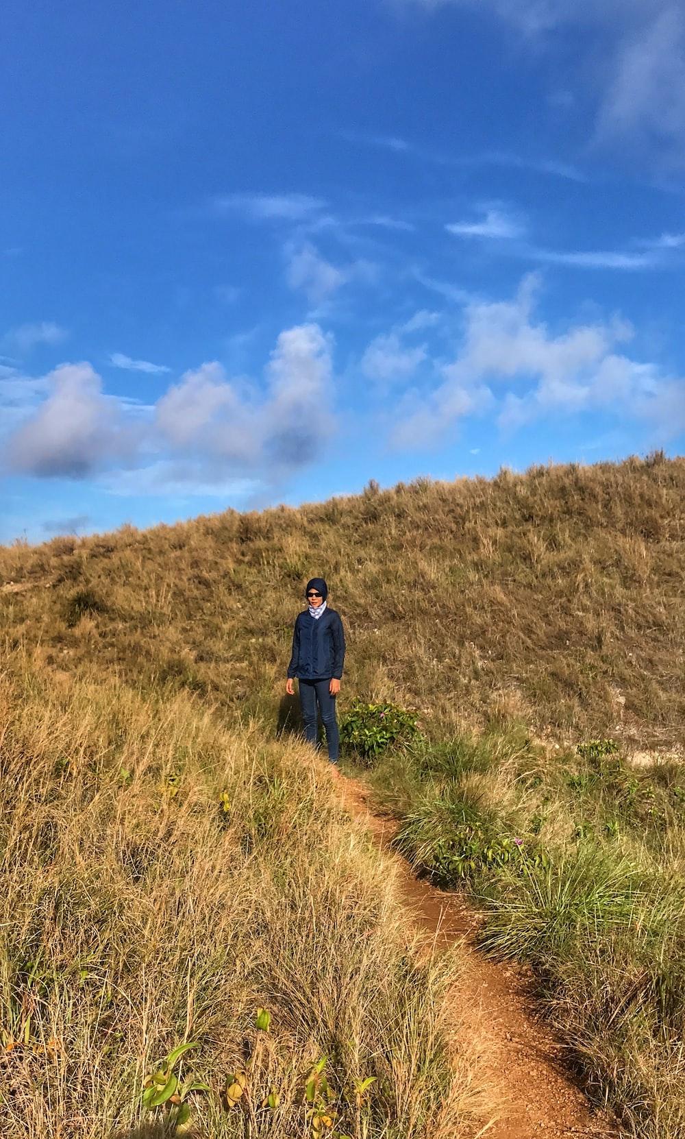 man standing beside grass