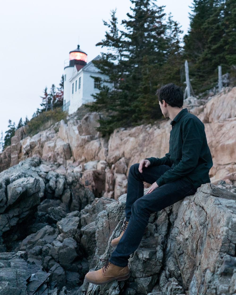 man wearing black dress shirt sitting on rock