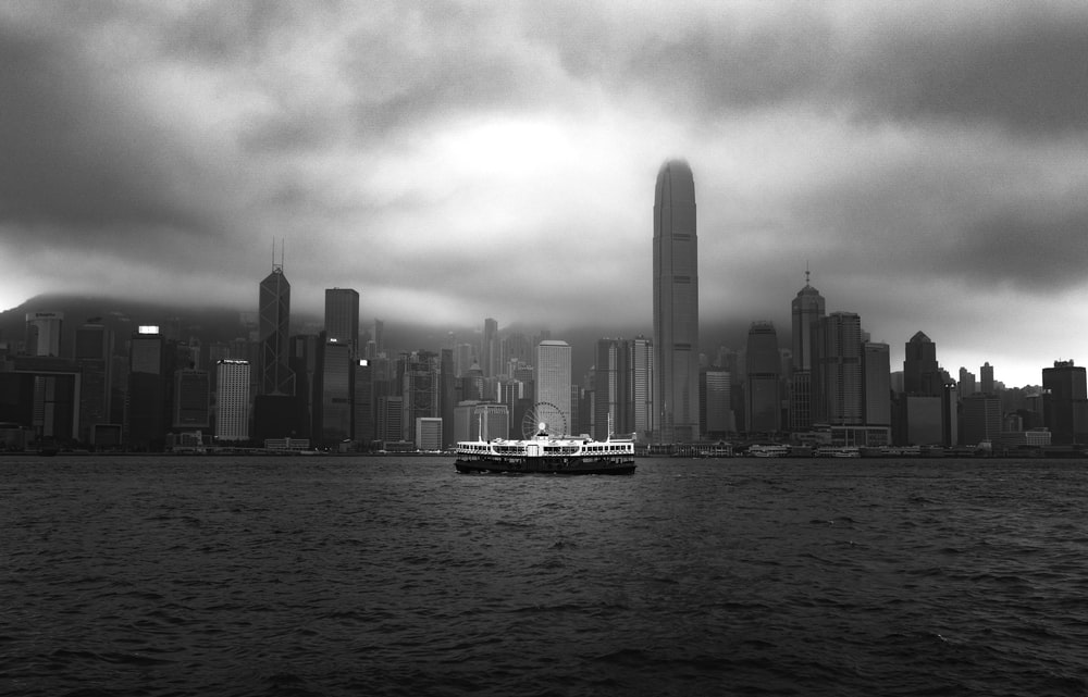grayscale photo of boat near buildings