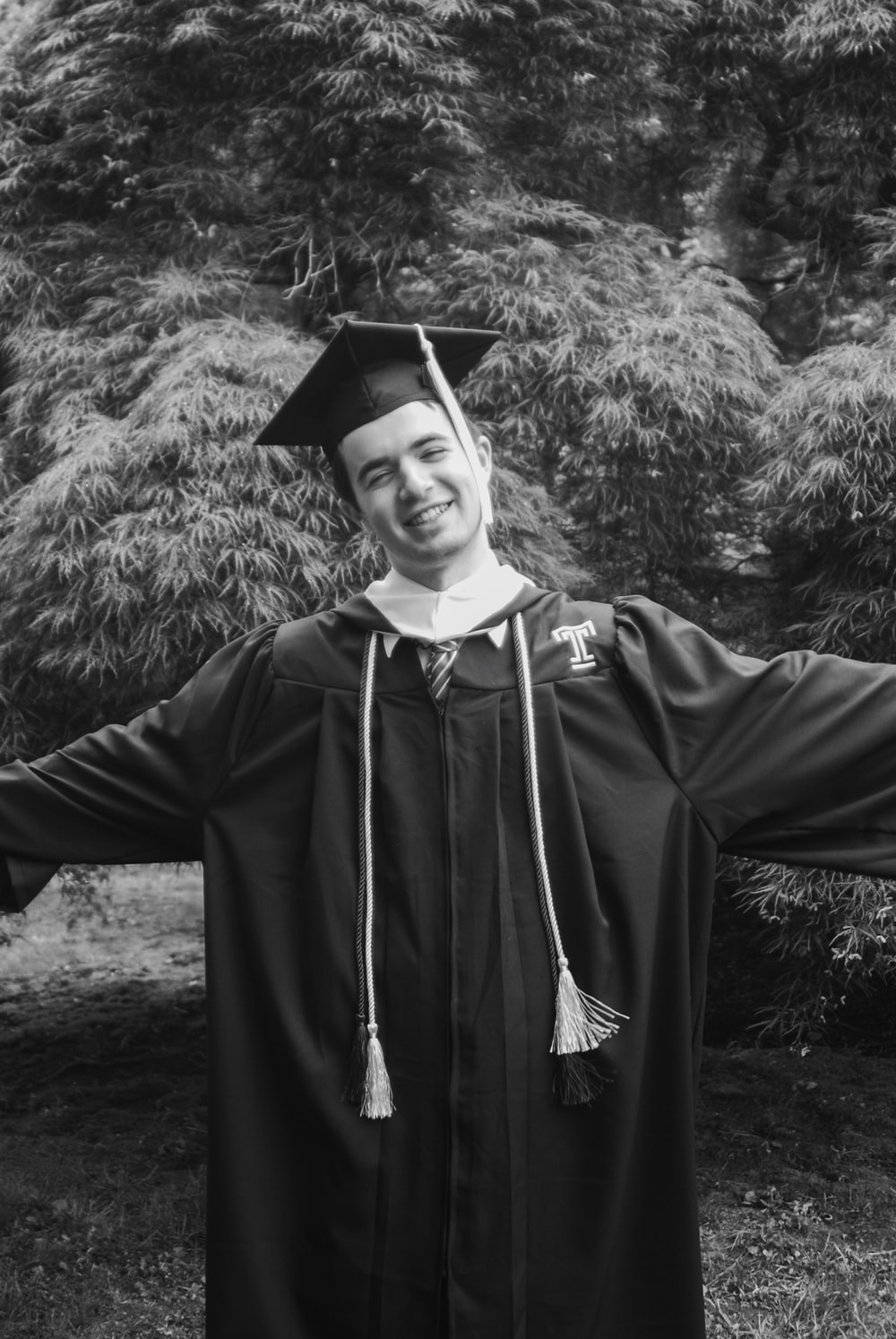 grayscale photography of man wearing academic dress