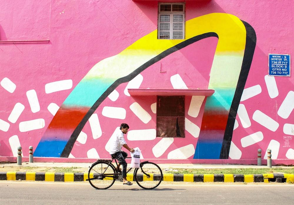 man riding bicycle along pink building