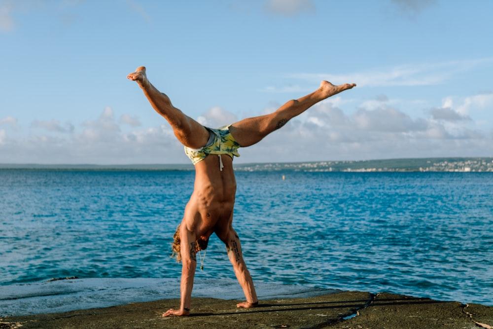 man standing using hands near sea