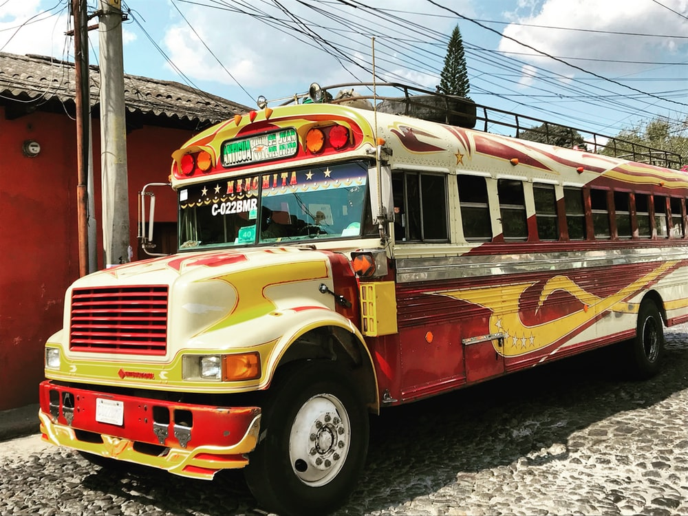yellow and red bus near street post
