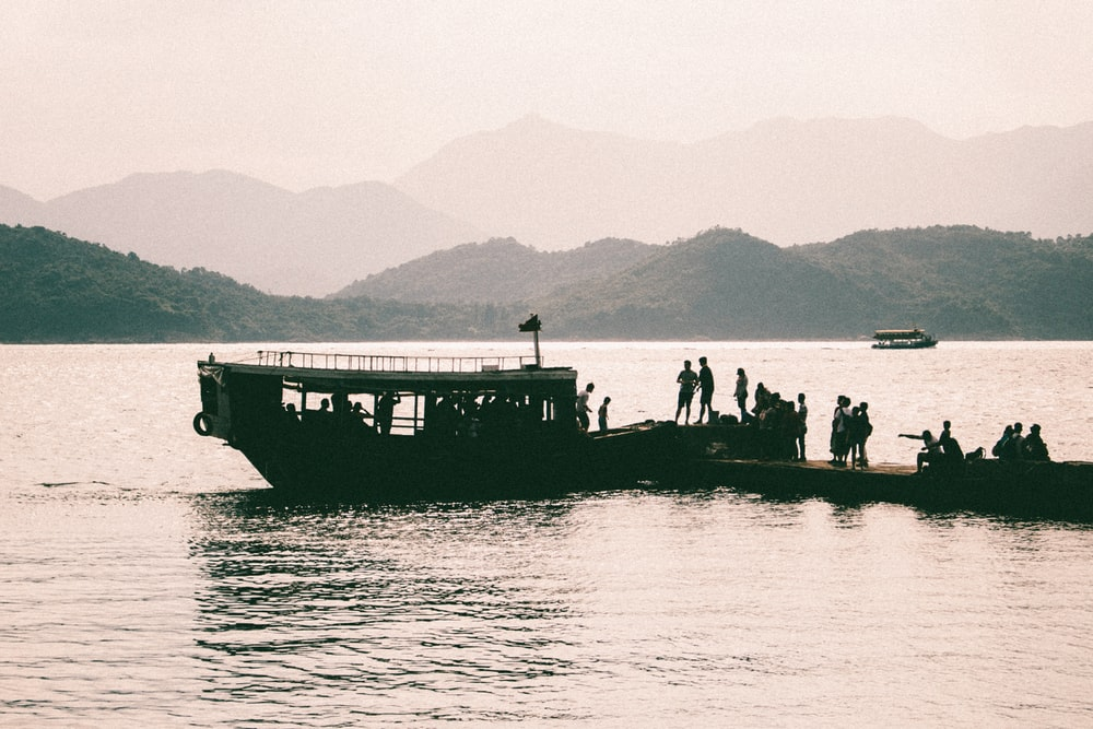 silhouette of people riding a boat