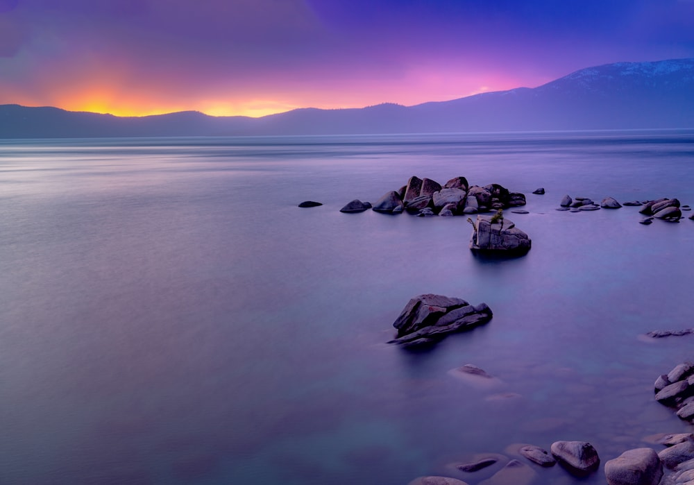 rock formations viewing blue sea and mountain during sunrise