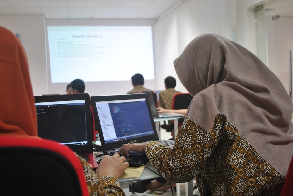 woman wearing grey hijab using laptop compiter