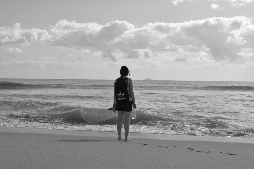woman standing near seashore facing back