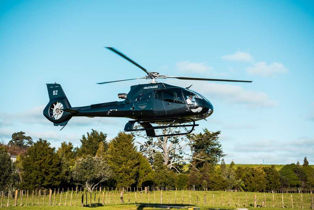 black helicopter near trees