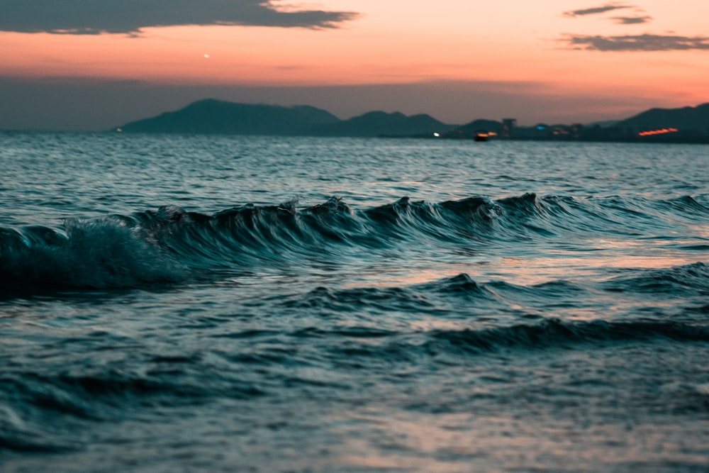wave rolling to the shore during sunset